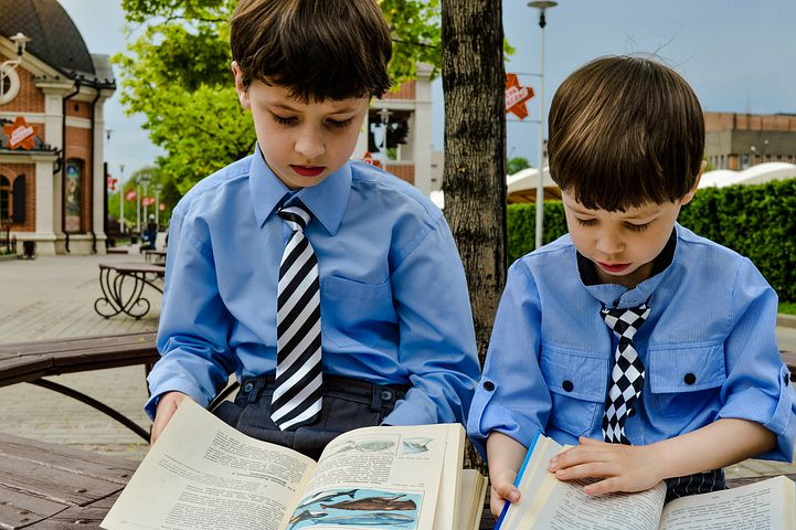 Kids in their uniform while reading a book