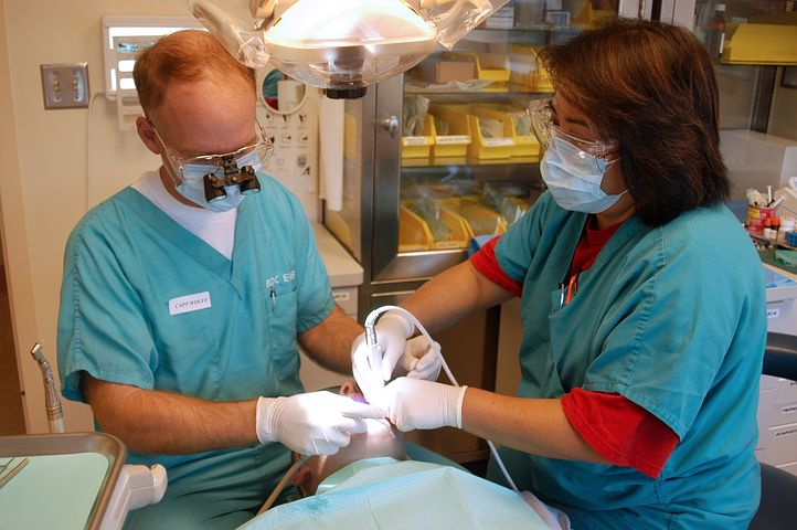 two dentists performing wisdom teeth removal procedure to a patient