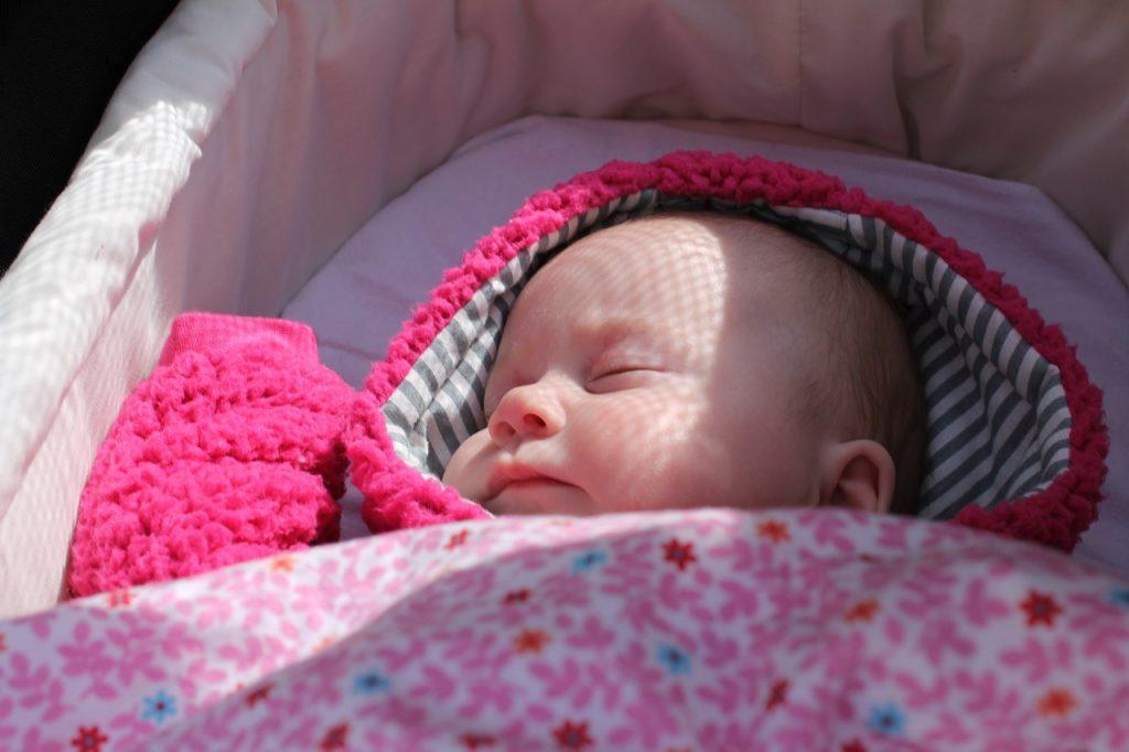 little baby sleeping in a baby pram