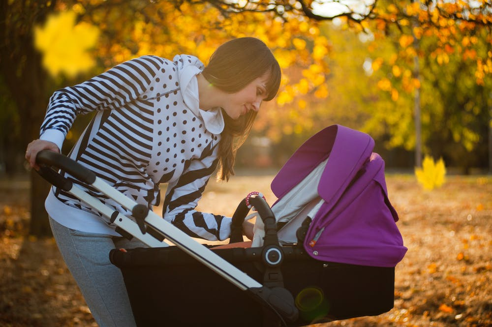Mother looking at her child in a baby pram in pink color