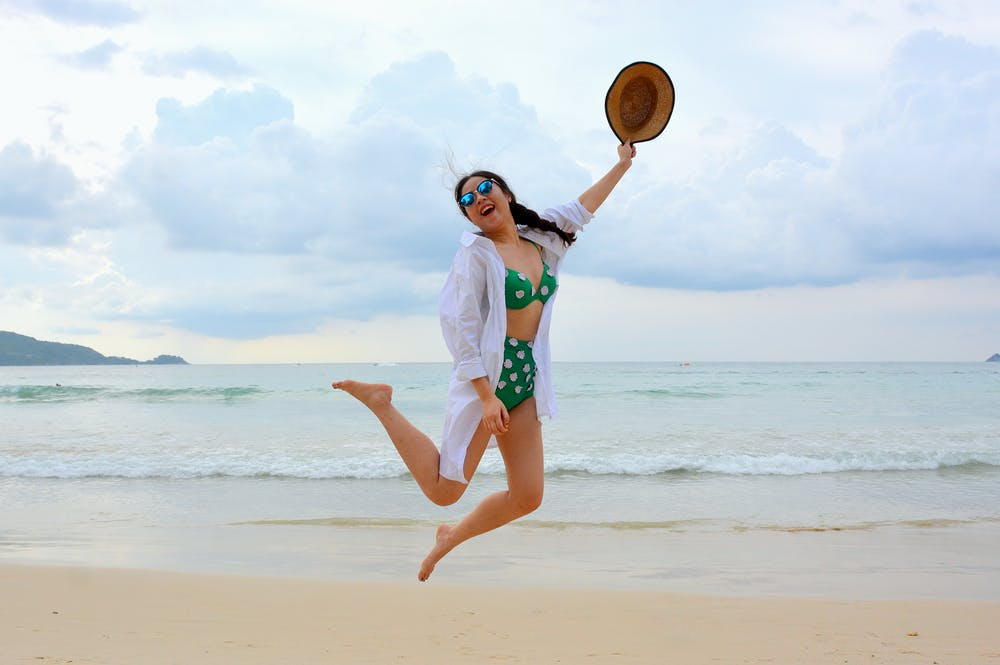 woman jumping while wearing her high waisted thong bikini