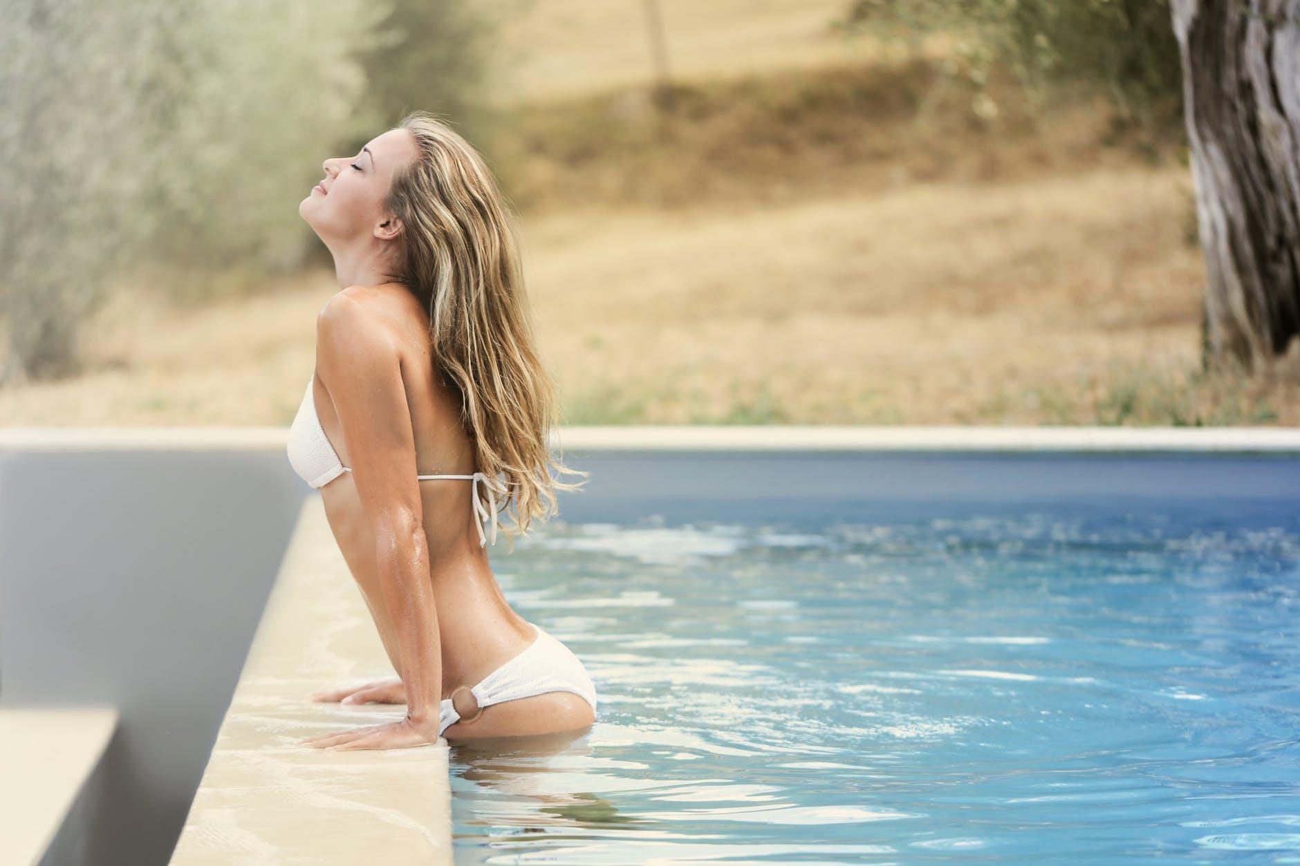 Woman wearing high waisted thong bikini, getting out of the pool