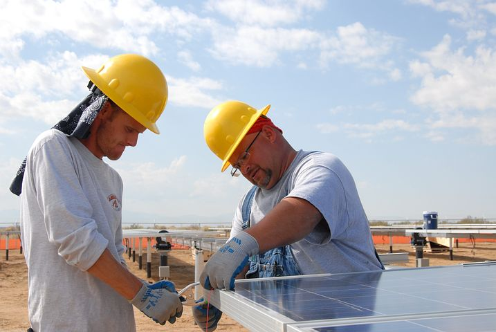 Worker installing commercial solar panels