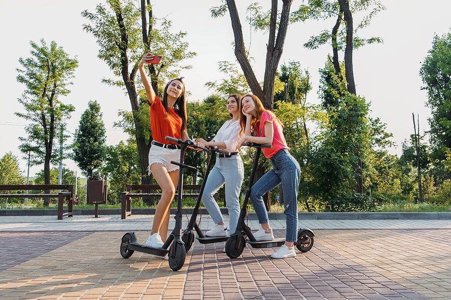 Three women riding Sydney electric scooters